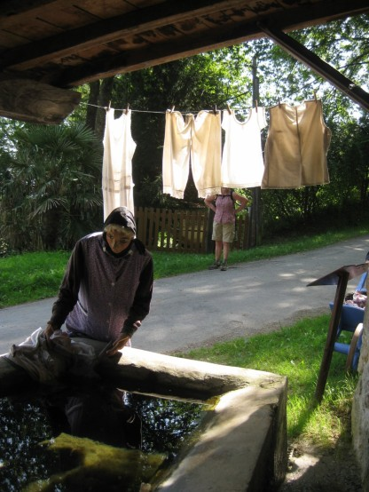 A woman at the village lavoir, or clothes washing place. Sinks are fed from a natural water source and sheltered by a roof. One of the centres of village life.