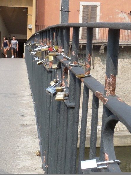 Lovers' padlocks , or bike locks on a bridge over the Onyar?