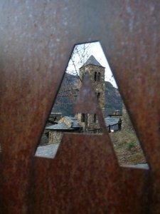 The Romanesque church at Aubinyà glimpsed through a village gate