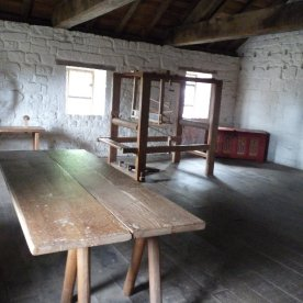 His upstairs workroom, with weaving loom and table.