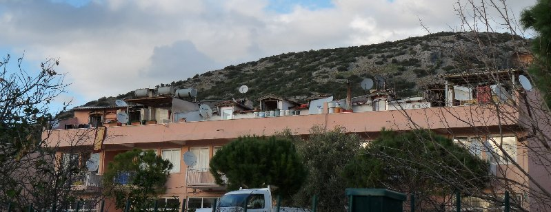 A block of flats with solar heating captors and satellite dishes.