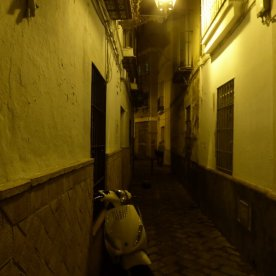 A narrow street by night.
