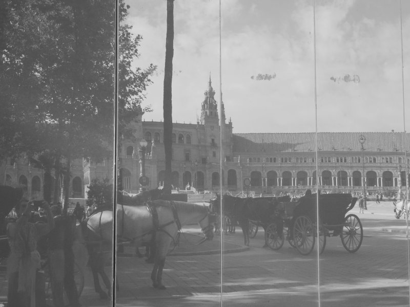 A view of Plaza de España, and the popular horse-drawn carriages of Seville, seen reflected in the windows of the public toilets.