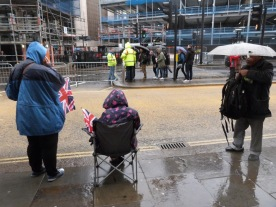 Avery British sight. An elderly woman waits patiently for the Lord Mayor's procession to wend its way past her again in .... oh, maybe an hour or so