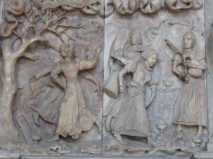 Carved wooden fire surround with music and dancing.