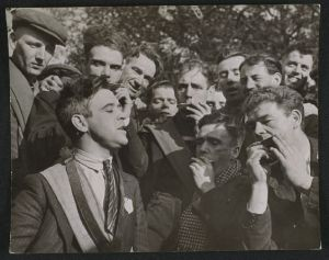 Photograph of J McCauley, a Jarrow marcher, singing to his co-marchers on their walk to London, taken in October 1936 by Edward G Malindine for the Daily Herald. The caption read ''Croonin' J McCauley, who helps to keep his co-marchers' spirits high, has been out of work for 5 years' (National Media Museum)