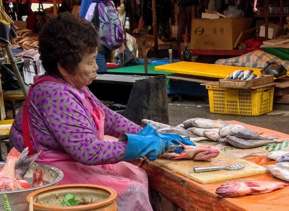 A woman filleting fish at Jagalchi Market, Busan, South Korea - perhaps the largest fish market in the world.